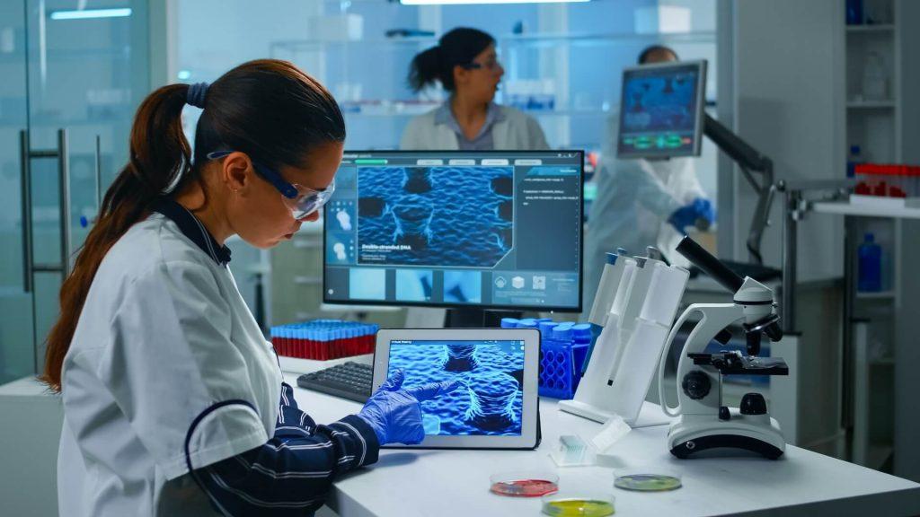 Lab technician doctor analyzing virus evolution looking on digital tablet
