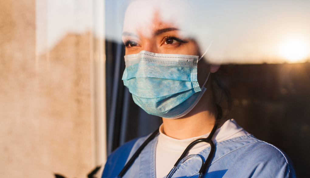 A woman wearing medical mask and looking through a window into the future